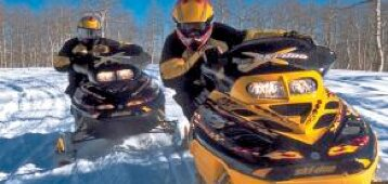 two snowmobiles with riders