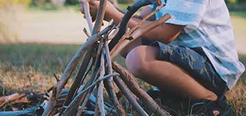 kid sitting on ground with sticks in pyramid shape