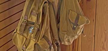tan backpacks hanging on a coat rack
