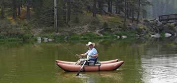 raft boat in water with man fishin from it