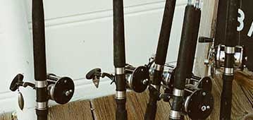 fishing rods leaned against a white wall