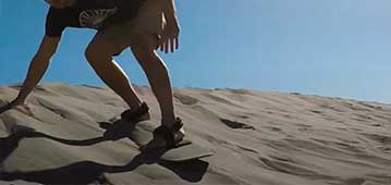 man sandboarding at Bruneau Dunes
