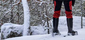 person standing in snow on snowshoes
