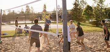 people playing volleyball outside on sand court