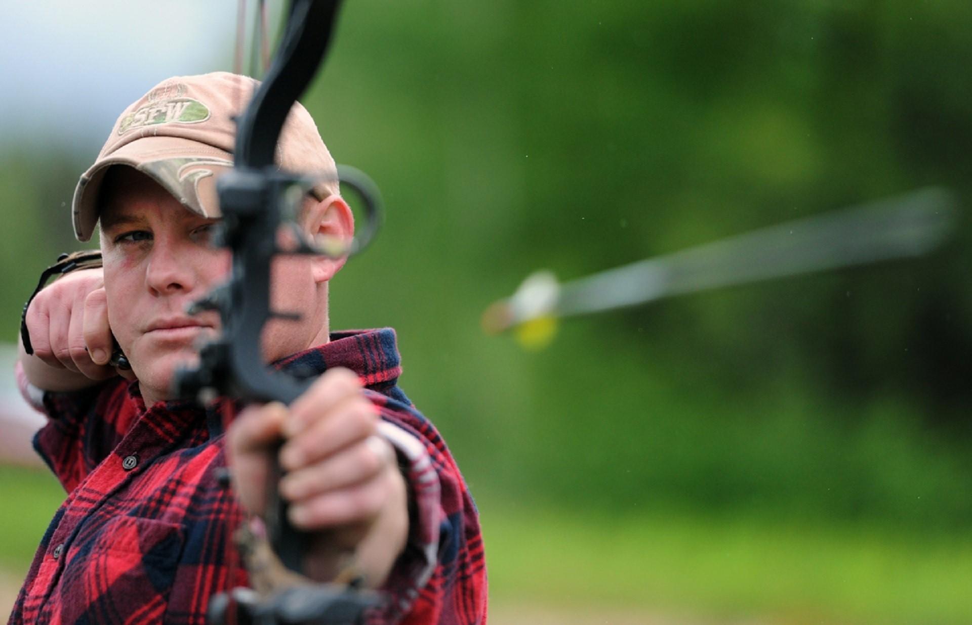 Man in plaid shirt firing an arrow