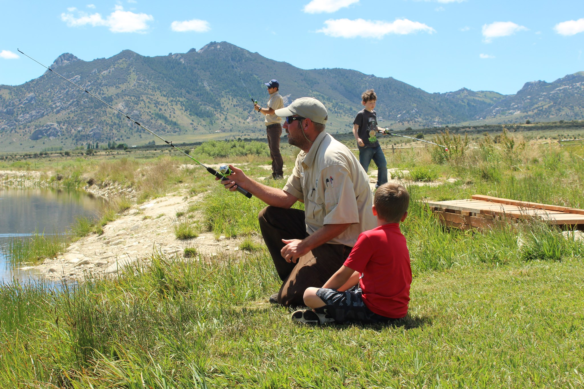 Park rangers teaching children how to fish. Image shows two rangers and two children