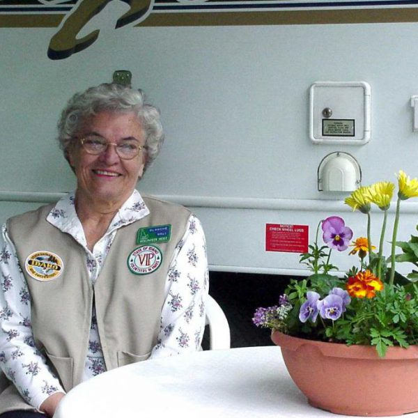 Farragut Host--Blanche Wall pictured in front of RV with flower pot