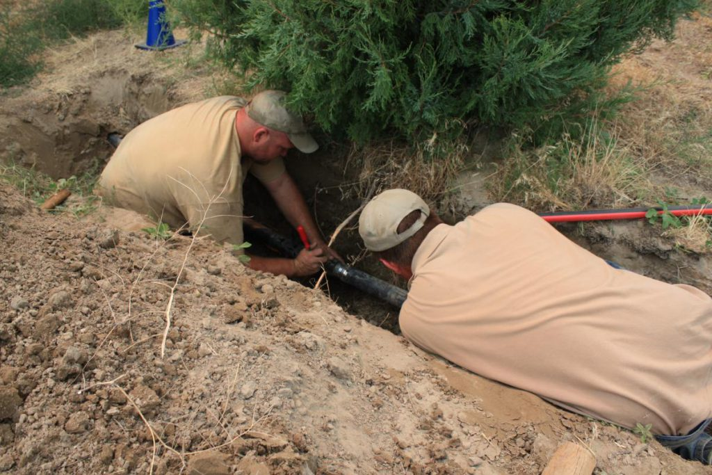 two employees working in trench in the ground