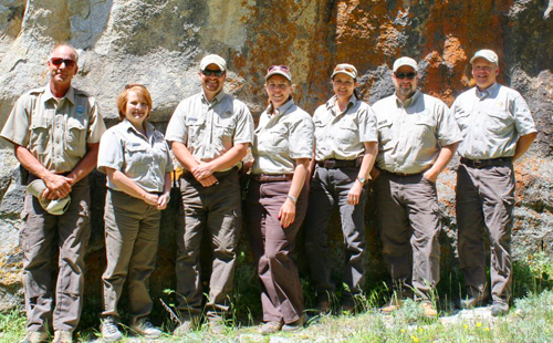 Parks and Recreation staff pictured in front of a large rock