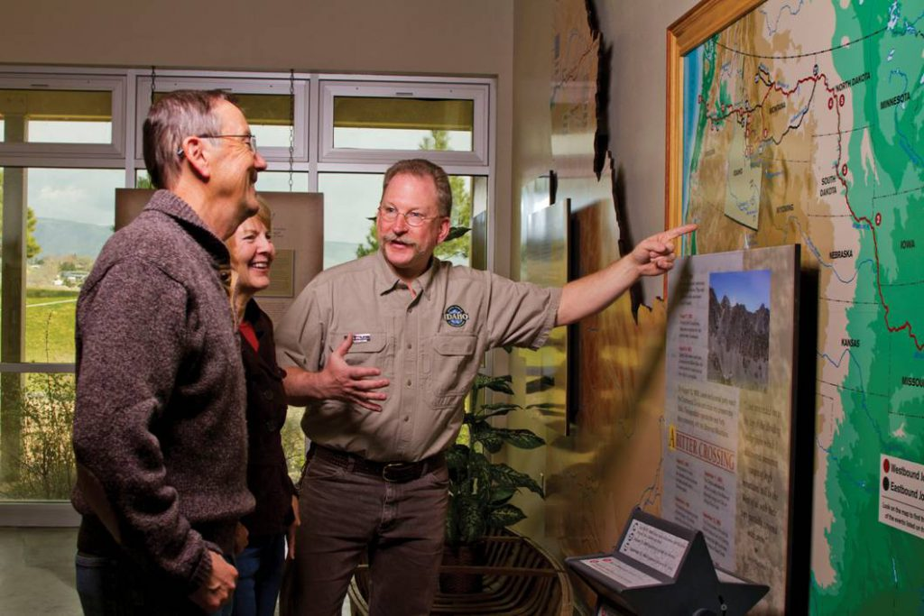 man showing guests large map on wall