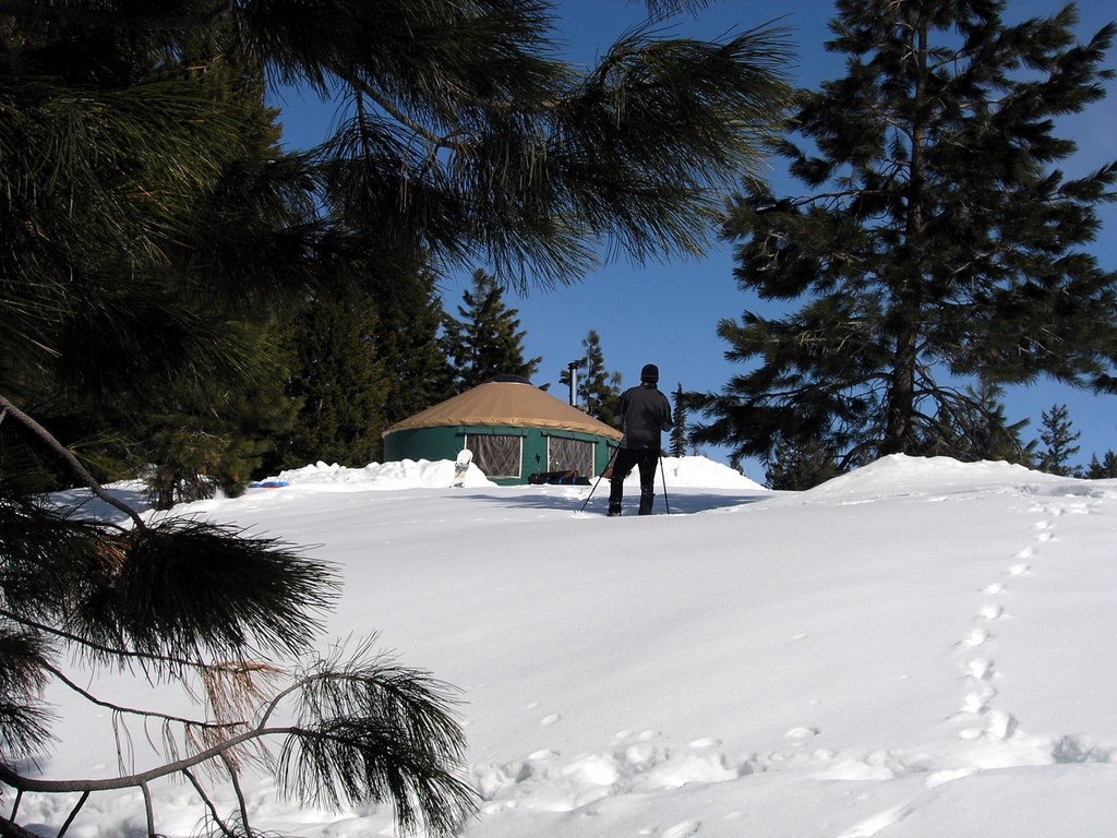 person skiing in front of yurt