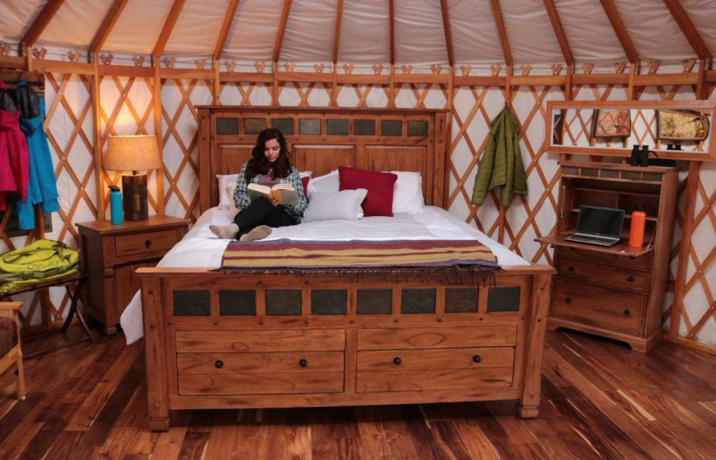 Inside the glamping yurt at Castle Rocks. Woman reading on king sized bed