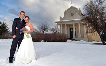 couple in wedding dress and tux in front of old mission