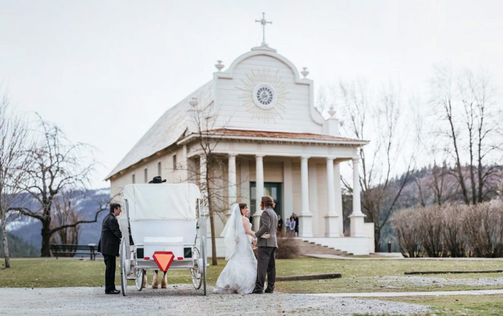 couple posing in front of old mission with a carriage