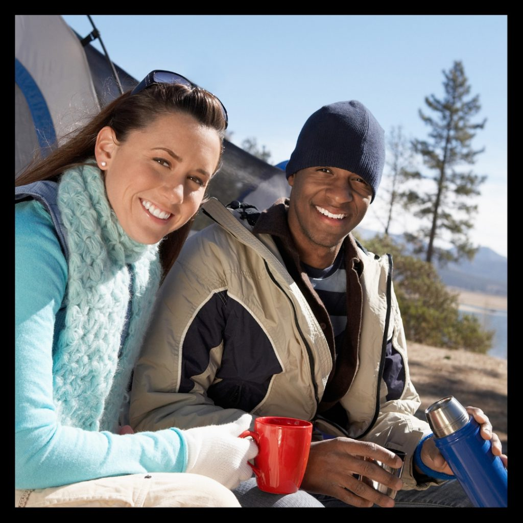 smiling man and woman by tent